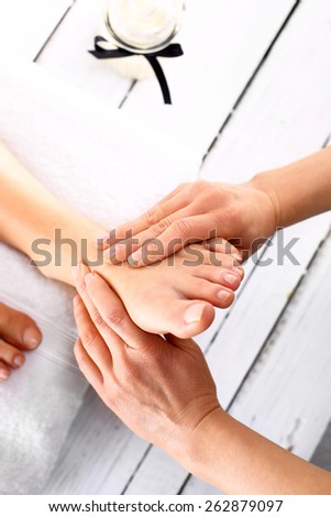 Foot massage in the spa salon. Woman in a beauty salon for pedicure and foot massage. - stock photo
