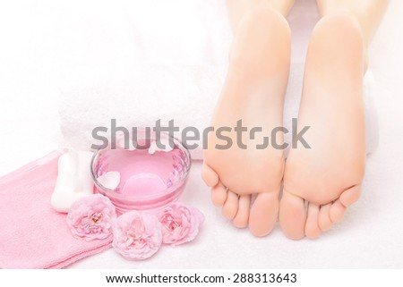 Foot massage in the spa with pink rose - stock photo