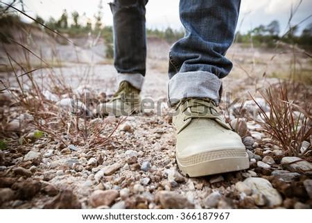 Foot of man walking on ground rock - stock photo