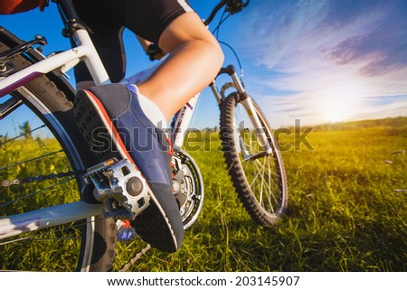 foot on pedal of bicycle. active summer - stock photo