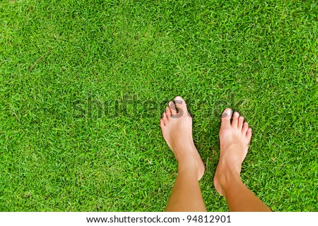 Foot over green grass - stock photo