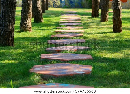Foot path in the grass, made from concrete plates. - stock photo