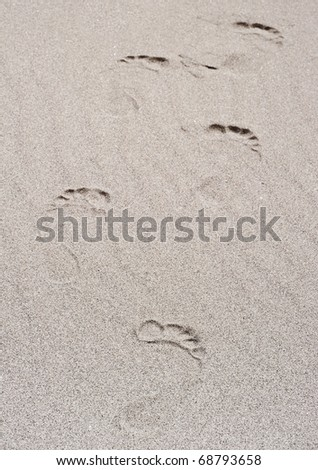 Foot prints going over a sand dune - stock photo