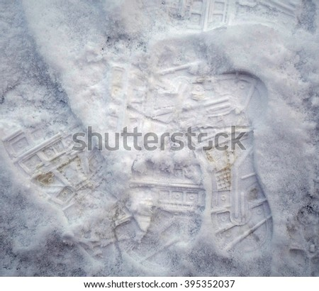 Foot Prints In Winter Snow Texture - Foot Prints in white snow on the ground, top view winter season tracks texture photo. - stock photo