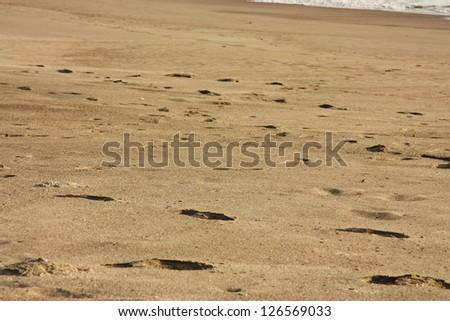 Foot prints on a beach. - stock photo