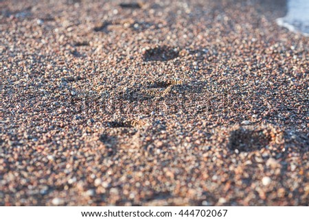 Foot prints on the beach sand by the sea with wave - stock photo
