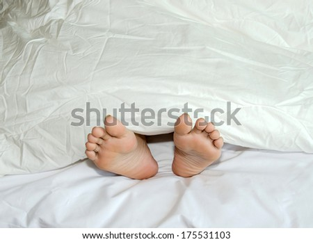 Foot rests on a bed covered with a white cloth. - stock photo