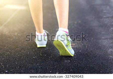 Foot Woman running on pavement - stock photo