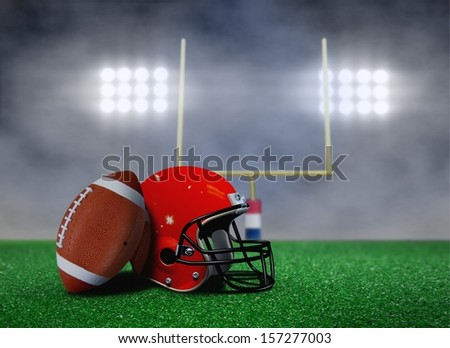 Football and Helmet on Field with Goal Post under Spotlights - stock photo