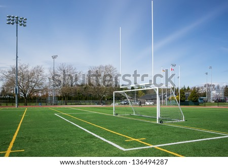 Football and soccer gates on artificial turf field. - stock photo