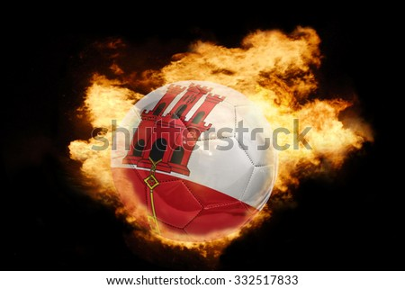 football ball with the national flag of gibraltar on fire on a black background - stock photo