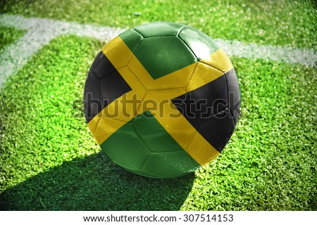 football ball with the national flag of jamaica lies on the green field near the white line - stock photo