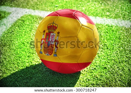 football ball with the national flag of spain lies on the green field near the white line - stock photo
