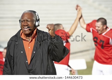 Football coach shouting and pumping fist with football players in the background - stock photo