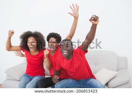 Football fans sitting on couch cheering together at home in the living room - stock photo