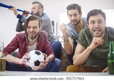 Football fans watching match at home - stock photo