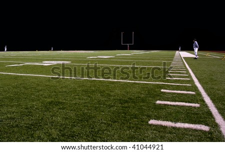 Football field at night with referees - stock photo