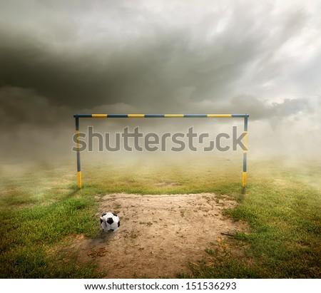 Football field, football goal, deflated ball and cloudy sky - stock photo