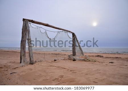 Football gate at empty beach - stock photo