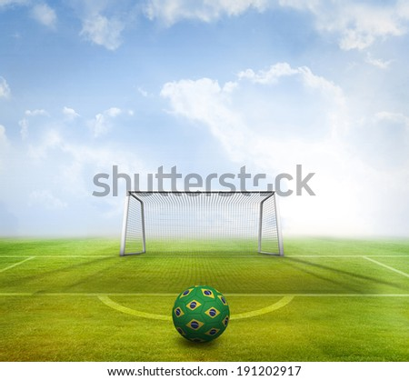 Football in brazilian colours against football pitch and goal under blue sky - stock photo