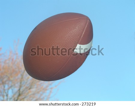 Football in the air - sky and trees in background - stock photo