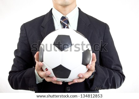 Football manager hold ball with his hands in studio - stock photo