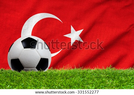 Football on grass field with wave flag of Turkey - stock photo