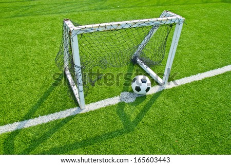 football on green grass with goal  - stock photo