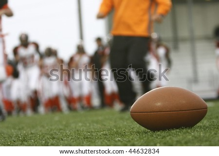 Football on the field with players and coach in the background. - stock photo