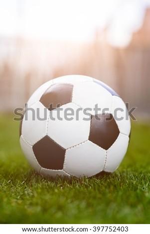 Football or soccer ball on green grass. Sunlight effect - stock photo