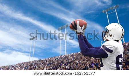 Football Player catching a Touchdown Pass - stock photo