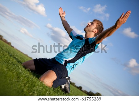 Football player celebrating with arms open outdoors - stock photo