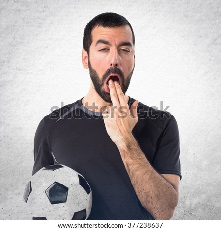 Football player doing vomiting gesture over textured background - stock photo