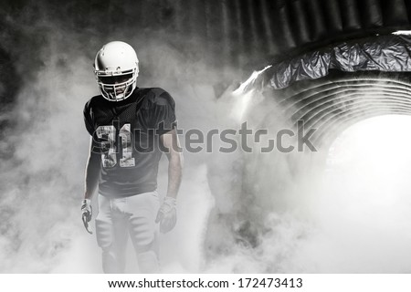 Football player in a black uniform, leaving a smoky tunnel, ready to get on the field - stock photo