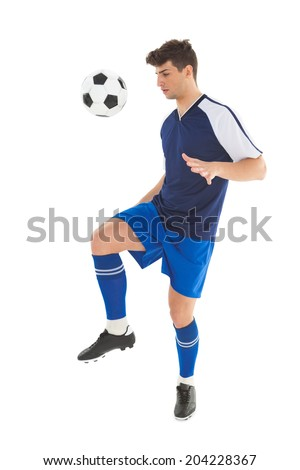 Football player in blue jersey kicking ball on white background - stock photo