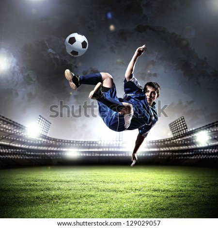 football player in blue shirt striking the ball aloft at the stadium - stock photo