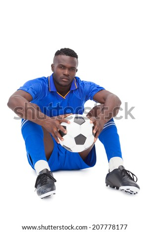 Football player in blue sitting with ball on white background - stock photo