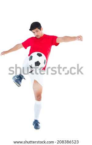 Football player in red kicking ball on white background - stock photo