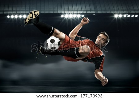 football player in red shirt striking the ball - stock photo