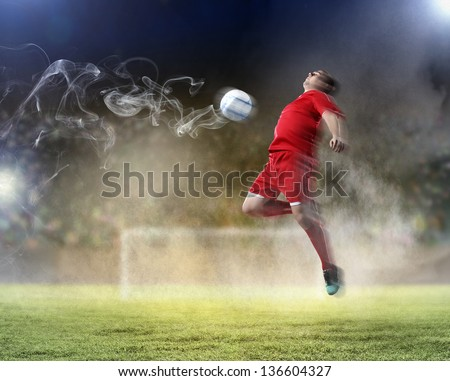 football player in red shirt striking the ball at the stadium - stock photo