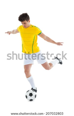 Football player in yellow jersey kicking ball on white background - stock photo
