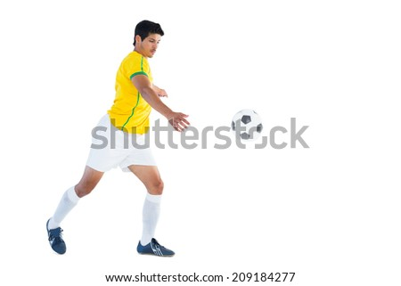 Football player in yellow kicking ball on white background - stock photo