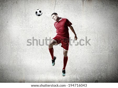Football player kicking ball against cement background - stock photo