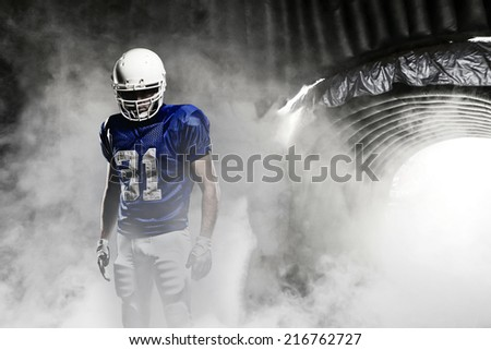 Football player, on a blue uniform, leaving a smoky tunnel, ready to get on the field. - stock photo