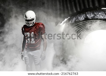 Football player, on a red uniform, leaving a smoky tunnel, ready to get on the field. - stock photo