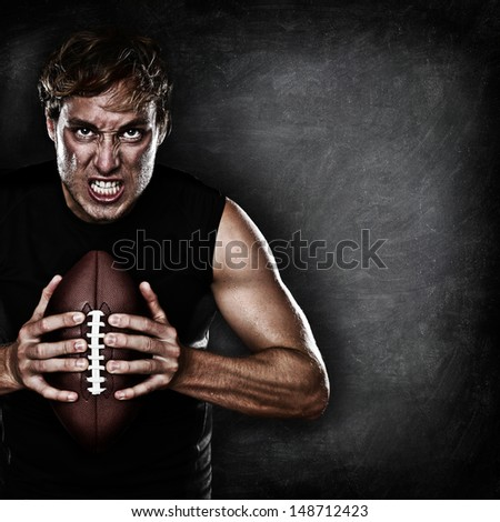 Football player portrait holding american football staring aggressive looking at camera on black chalkboard background with copy space for text or design. Caucasian male model in his 20s. - stock photo