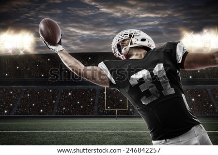 Football Player with a Black uniform catching a ball on a stadium. - stock photo