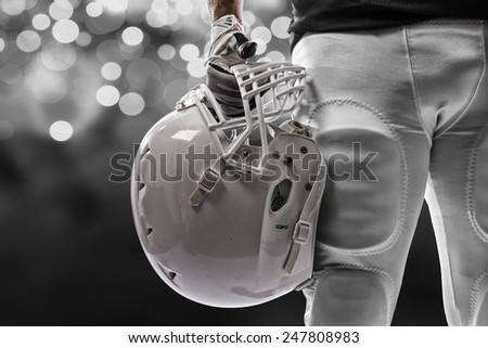 Football Player with a black uniform on a black lights background. - stock photo
