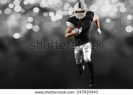 Football Player with a black uniform Running on a black lights background. - stock photo