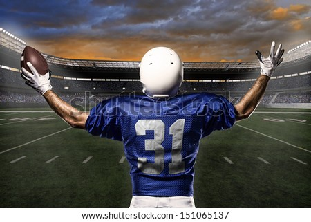 Football Player with a blue uniform celebrating with the fans. - stock photo
